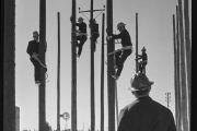 Fotos para la historia: Grupo de trabajadores subidos en postes de luz equipados con materia de seguridad